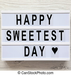 'Happy Sweetest Day' word on modern board over white wooden background, top view. From above, flat lay, overhead.