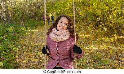 Happy Swinging - Beautiful young lady enjoying swinging in...
