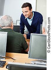 Happy Teacher Assisting Senior Student In Computer Classroom
