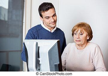 Happy Teacher Helping Senior Student In Computer Class