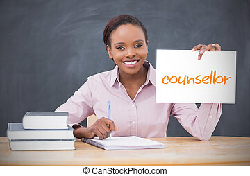 Happy teacher holding page showing counsellor in her classroom at school