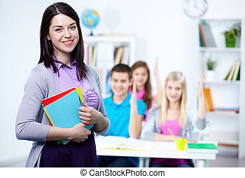 Happy teacher looking at camera with her students on...