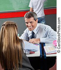 Happy Teacher Teaching Little Girl At Desk