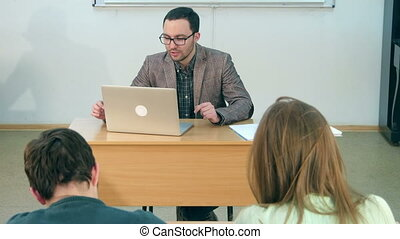 Happy teacher with laptop giving lesson to a class