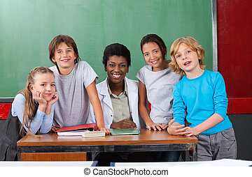 Happy Teacher With Students At Desk