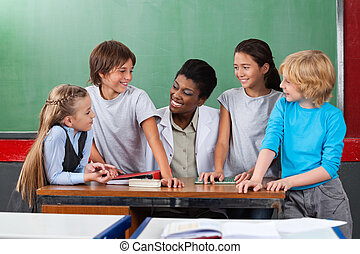 Happy Teacher With Students Communicating At Desk