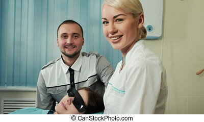 Happy team of dentist and nurse with patient in dental office.