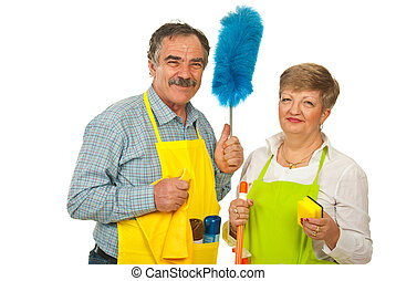 Happy team of mature cleaning people holding objects...