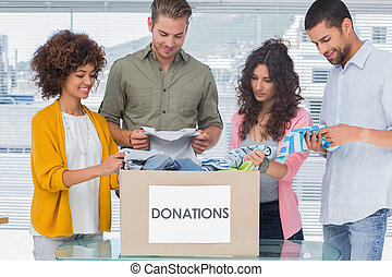 Happy team of volunteers taking out clothes from a donation box