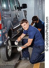 Happy Technician Fixing Car Tire At Workshop