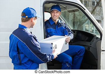 Happy Technician Giving Toolbox To Colleague