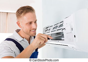 Happy Technician Repairing Air Conditioner
