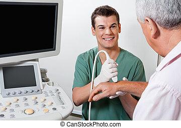 Happy Technician Scanning Male Patient's Hand