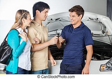 Happy Technician Taking Car Keys From Couple