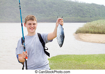 teen boy showing a fish he just caught