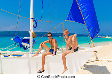 Happy teen boys on the sailboat on the tropical beach. Summer vacation concept