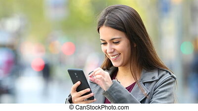 Happy teen browsing on phone in the street