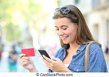 Happy teen buying online with a smartphone in the street