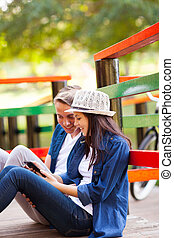 happy teen couple using tablet computer outdoors
