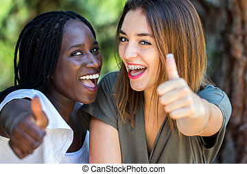 Happy teen diverse couple doing thumbs up.
