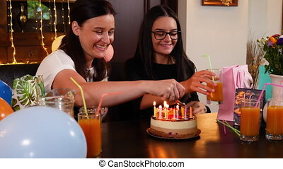 Happy teen girl and mother with birthday cake at anniversary...