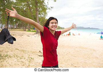 Happy teen girl arms raised wide on hawaiian beach