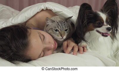 Happy teen girl communicates with dog Papillon and Thai cat...