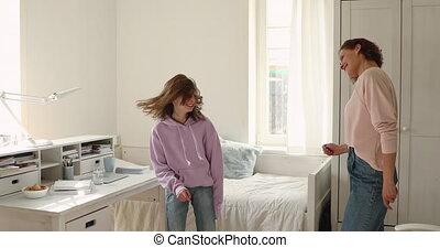 Happy teen girl dancing to energetic loud music with mom.
