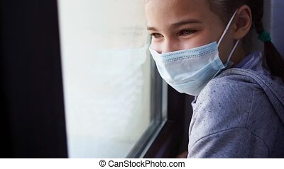 a happy teen girl in a protective mask, look out of the window outside, waving his hand, meets his parents. she is sick and self-isolating during the pandemic.