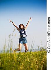 Happy teen girl jumping over blue sky. Beauty girl having fun outdoor