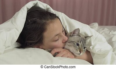 Happy teen girl kisses and talks with Thai cat in bed stock...