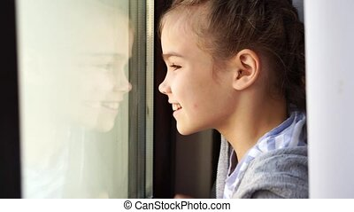a happy teen girl look out of the window outside wave his hands, meets parents. she is recovered and self-isolating during the pandemic. distance learning.