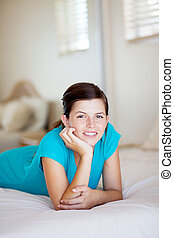 happy teen girl lying on her bed at home
