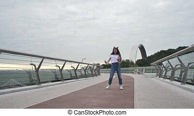 Happy teen girl performing stylish dance on bridge - Joyful ...