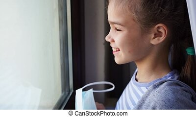 a happy teen girl removes a protective mask, look out of the window outside. she was ill and is recovering. self-isolating during the pandemic.