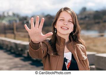 Happy teen girl showing five