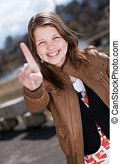 Happy teen girl showing one