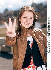 Happy teen girl showing three