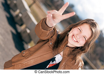 Happy teen girl showing victory or peace sign