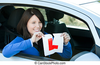 Happy teen girl sitting in her car