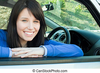 Happy teen girl smiling at the camera sitting in her car