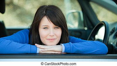 Happy teen girl smiling in her car