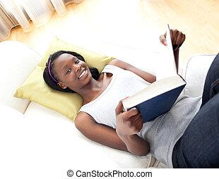 Happy teen girl studying lying on a sofa