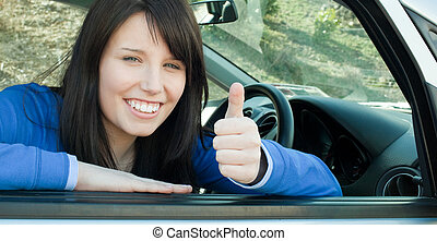 Happy teen girl with a thumb up sitting in her car