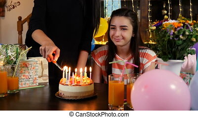 Happy teen girl with birthday cake at party