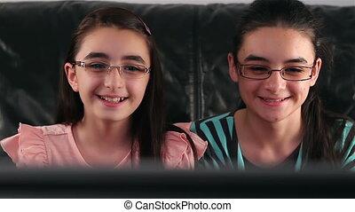 Happy teen girls watching tv - Happy teen girls with glasses...