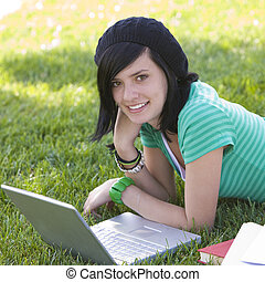 Happy teen in in grass with laptop - Teen studies with...