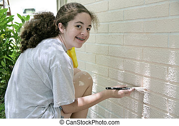 Happy Teen Painting House - A cute teen girl helping out by...