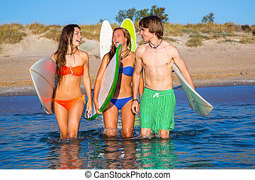 Happy teen surfers talking on beach shore
