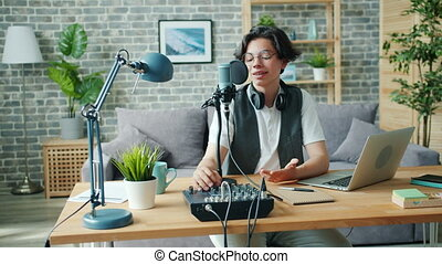 Happy teen boy is talking in microphone using sound mixer in studio recording podcast for internet blog. Modern technology, equipment and blogging concept.